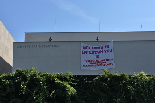 """Transparent am Mozarteum mit der Aufschrift: """"NOT HERE TO ENTERTAIN YOU!!! Studierende gegen S20 #mozarteum #nichtinunseremnamen"""""""