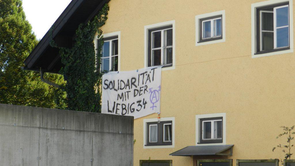 """Ansicht des Hauses, aus den Fenstern hängt ein Transparent mit der Aufschrift """"Solidarität mit der Liebig 34"""" und einem Anarcha-queer-feministischen Symbol"""
