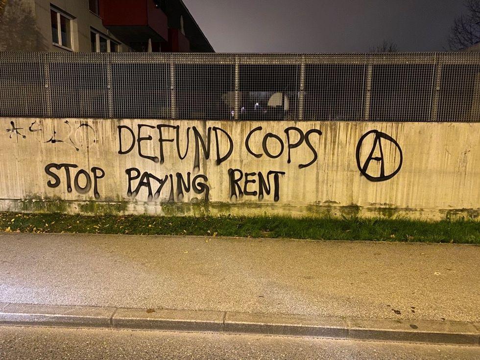 """Foto von Graffiti: """"Defund cops (Anarchie-A) Stop paying rent"""""""