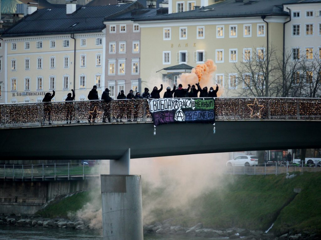 """Foto einer Gruppe von ca. 15 vermummten Personen auf dem Feingold-Steg, im Hintergrund die Salzburger Altstadt. An der Brücke hängt ein Transparent mit der Aufschrift """"Free anarchist prisoners"""""""