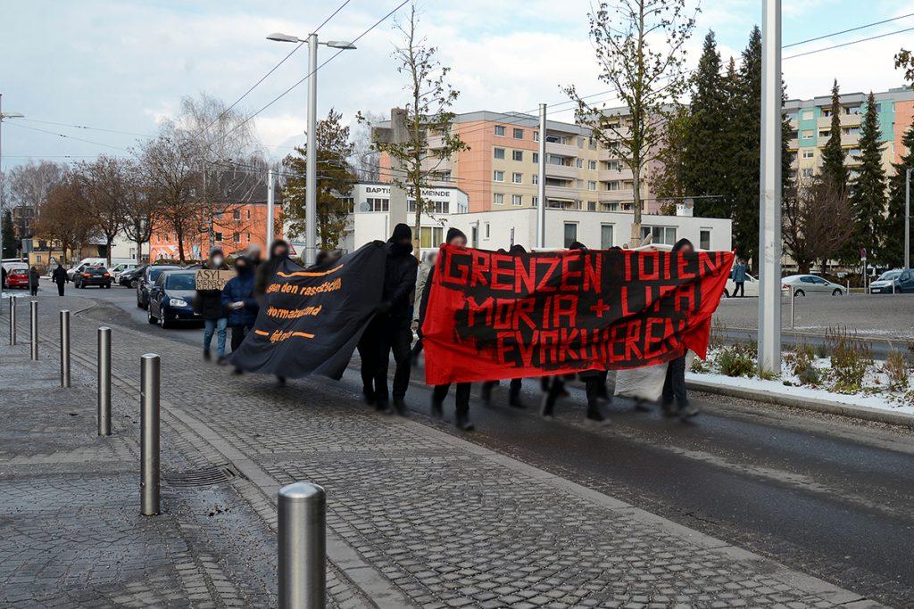 """Foto der Spontandemo. Rotes Front-Transparent mit der Aufschrift """"Grenzen töten. Moria und Lipa evakuieren"""". Schwarzes Seiten-Transparent mit der Aufschrift """"Gegen den rassistischen Normalzustand. Fight racism"""""""