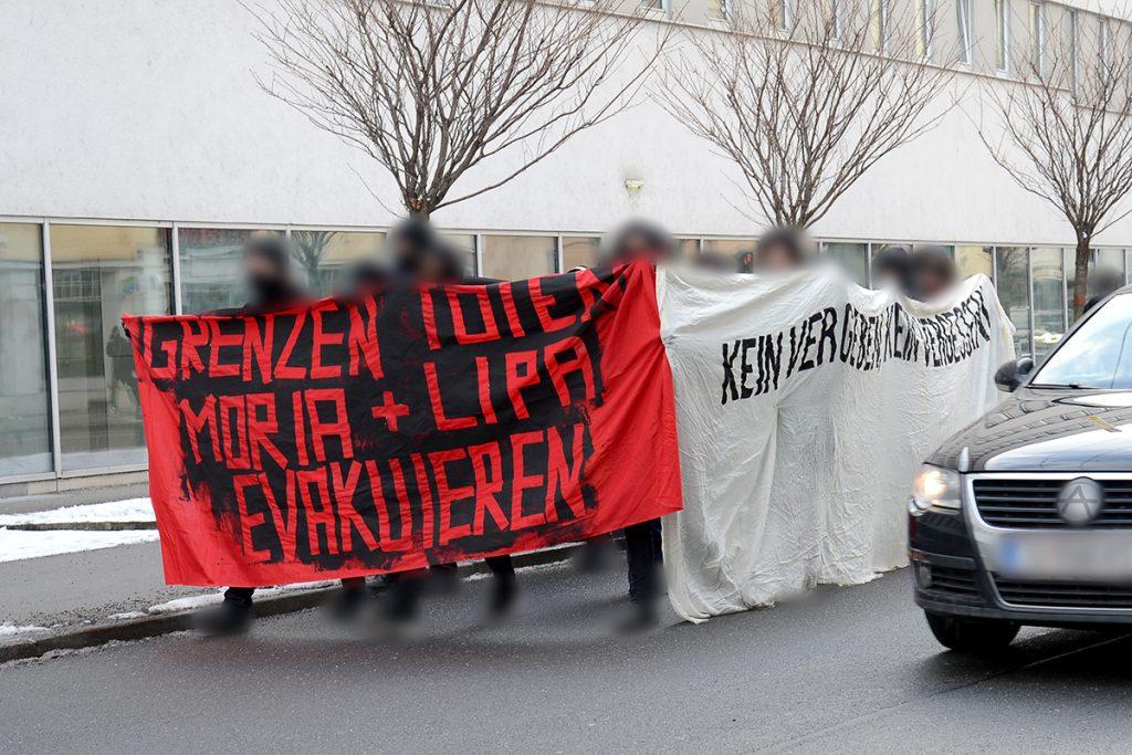 """Foto der Spontandemo. Rotes Front-Transparent mit der Aufschrift """"Grenzen töten. Moria und Lipa evakuieren"""". Weißes Seiten-Transparent mit der Aufschrift """"Kein Vergeben, kein Vergessen"""""""