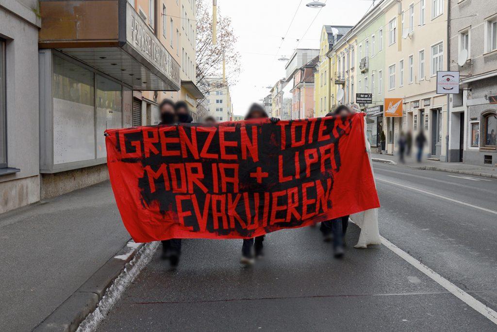 """Foto der Spontandemo auf der Ignaz-Harrer-Straße. Rotes Front-Transparent mit der Aufschrift """"Grenzen töten. Moria und Lipa evakuieren"""""""