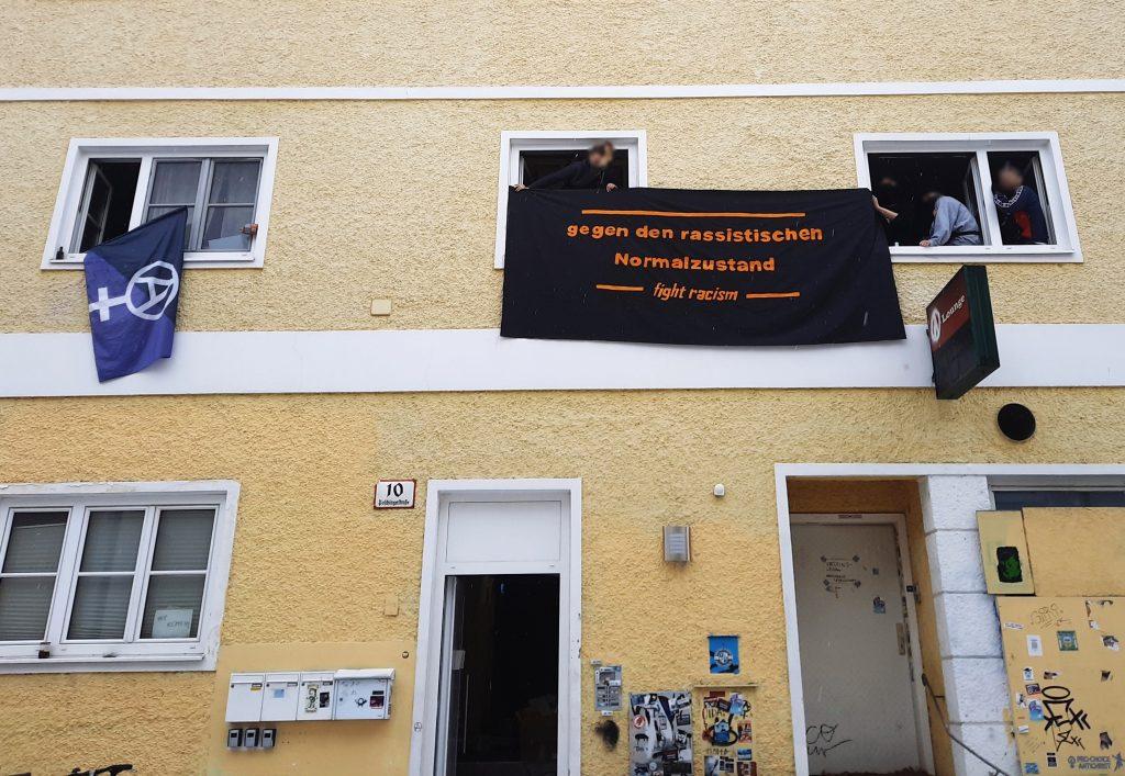 """Foto der Autonomen Wohnfabrik. Aus den Fenstern im ersten Stock hängen eine anarcha-feministische Fahne in schwarz und lila und ein schwarzes Transparent mit der Aufschrift """"Gegen den rassistischen Normalzustand. Fight racism!"""" In den Fenstern sind mehrere autonome Personen zu sehen."""