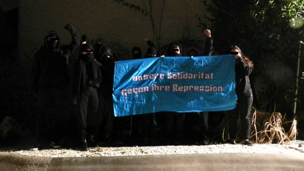 """Foto mehrer schwarz gekleideter und vermummter Personen mit einem blauen Transparent mit der Aufschrift """"Unsere Solidarität gegen ihre Repression"""""""