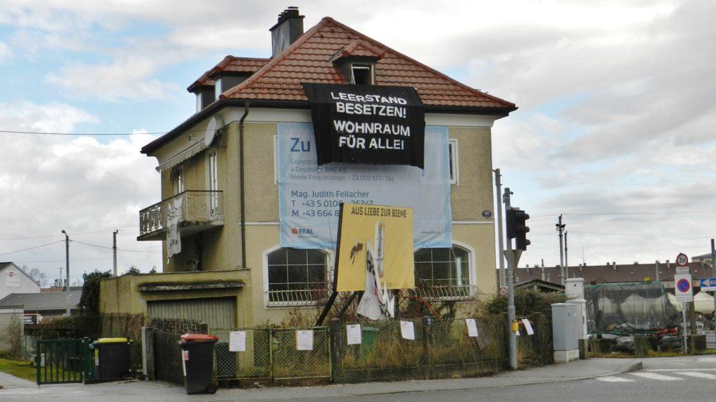 """Ein Foto des leerstehenden Gebäudes in der Vogelweiderstraße. Am Haus hängt ein großer Banner einer Immobilien-Firma. Der Garten des Hauses ist desolat und überwuchert. Aus dem der Straße zugewandten Dachfenster hängt ein großes schwarzes Transparent mit der Aufschrift """"Leerstand besetzen! Wohnraum für alle!"""". Am Gartenzaun hängen viele Plakate, offenbar von den Besetzer_innen angebracht."""