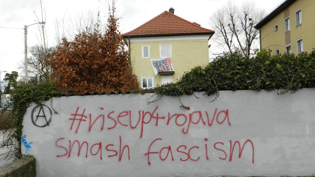 """Eine weitere Ansicht des Hauses, von weiter weg. Aus den Fenstern hängt ein Transparent mit der Aufschrift """"Effy29 lebt!"""". Im Vordergrund des Fotos sieht man eine Wand, auf die """"#RiseUp4Rojava – smash fascism"""" gesprüht wurde."""