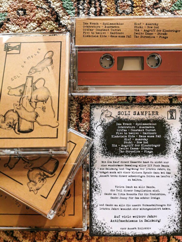 """Foto der Kassette. Auf dem Cover des Samplers sind das Anna96 Logo und der Text """"Soli Sampler"""" zu sehen, außerdem eine schwarz-weiß Illustration einer liegenden Bier- oder Limoflasche mit mehreren Mäusen. Die Tracklist des Samplers: Das Wrack – Spülmaschine; Gehörsturz – Ausrasten; Gitfas – Constant Unrest; Five to twelve – Hardcore; Klaheisla Kids – Raus ausm PAZ; Sluf – Anarchy; Stuhl – New God; 3DA – Angriff der Klonkrieger; Zweite Kasse – Straße; The Stroodles – Flags"""
