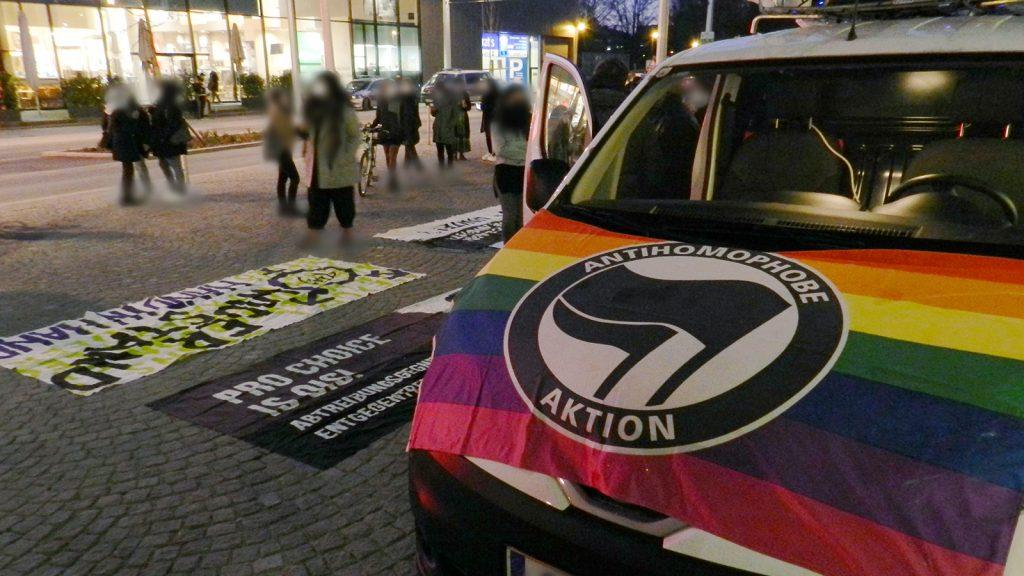 """Foto des Demo-Autos. Auf der Motorhaube ist eine Regenbogenfahne mit Antifa-Symbol befestigt (""""Antihomophobe Aktion""""). Im Hintergrund sieht man mehrere feministische Transparente."""