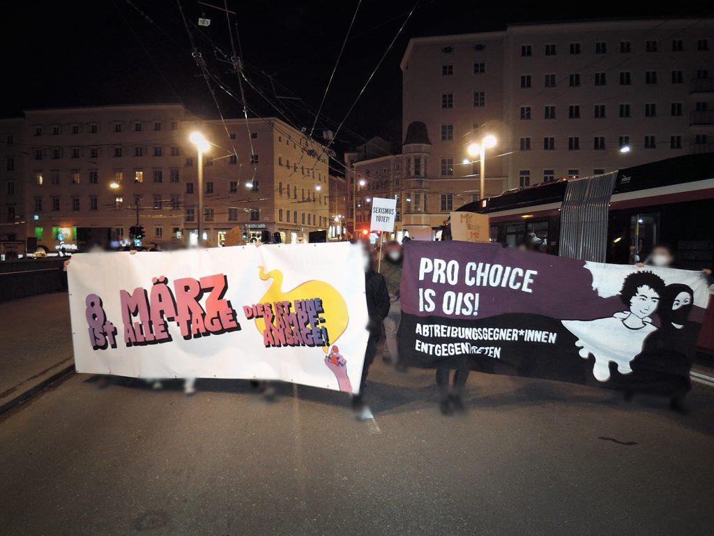 """Front-Ansicht der Demo. Es ist bereits nacht, die Straße ist durch Straßenbeleuchtung erhellt. Auf einem Transparent steht """"8. März ist alle Tage! Dies ist eine Kampfansage!"""", auf einem anderen """"Pro Choice is ois! Abtreibungsgegner*innen entgegentreten"""". Im Hintergrund sieht man ein Schild mit der Aufschrift """"Sexismus tötet!"""""""