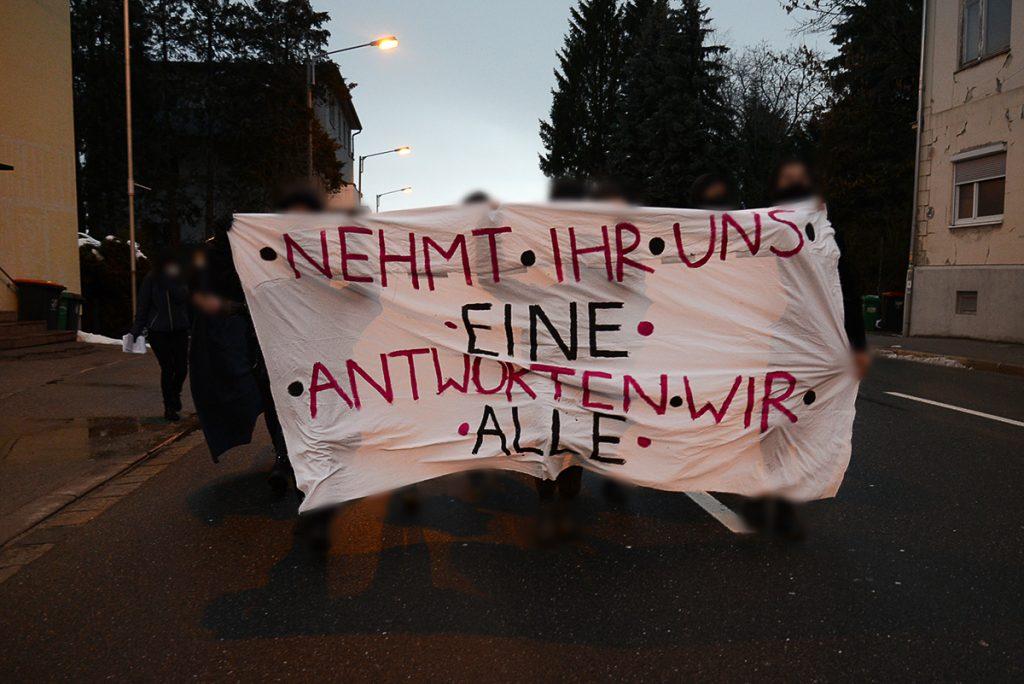 """Frontale Ansicht der Spontan-Demonstration. Auf dem weißen Front-Transparent steht """"Nehmt ihr uns eine, antworten wir alle!"""""""