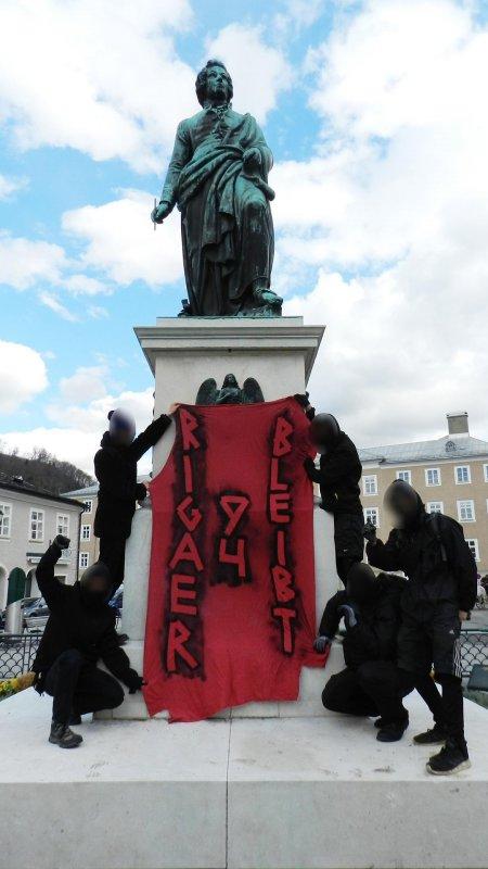 """Foto der Mozartstatue am Mozartplatz in Salzburg. Eine handvoll schwarz gekleideter und vermummter Aktivist_innen halten ein rotes Transparent mit der Aufschrift """"Rigaer 94 bleibt"""" vor die Statue."""