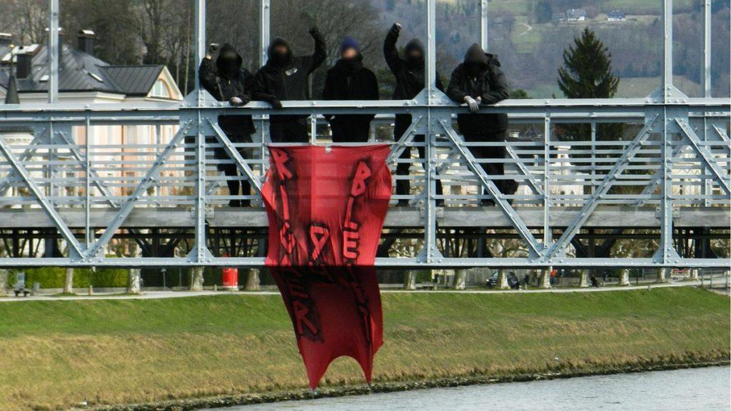 Foto des gleichen roten Transparents, das an einer Brücke an der Salzach hängt. Dahinter posieren die Aktivist_innen, zum Teil mit gehobenen Fäusten.
