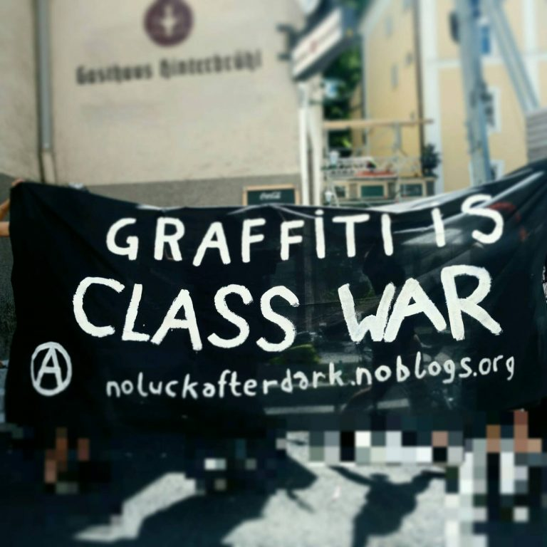"""Foto-Aufnahme bei der Kundgebung vor Gericht. Leute halten ein schwarzes Transparent mit Anarchie-A und der Aufschrift """"Graffiti is class war. NoLuckAfterDark.noblogs.org"""""""