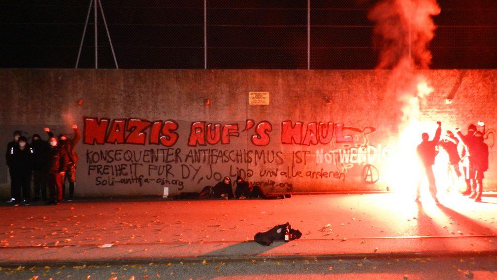 Ein Haufen vermummter Leute mit rotem bengalischem Feuer vor einem Graffiti. Text des Graffitis: Nazis auf's Maul! Konsequenter Antifaschismus ist notwendig! Freiheit für Dy, Jo, Lina und alle anderen! soli-antifa-ost.org – Daneben ist ein Anarchie A gesprüht.
